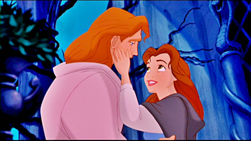 The beast turns into a prince. Belle caresses him